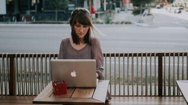 vrouw maakt cv op laptop en kijkt serieus