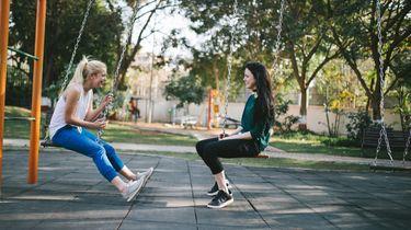 twee vriendinnen zitten op schommels en geven advies
