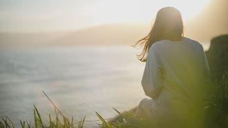 vrouw aan het mediteren op een berg