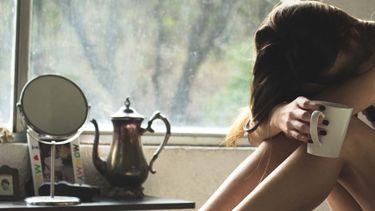 Zittend meisje op bed met hoofd in handen, migraine tips