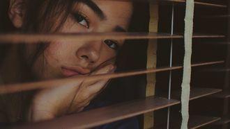 Verveeld meisje die uit het raam kijkt, verveling relatie vragen