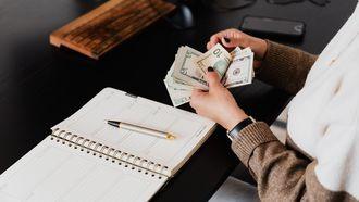 vrouw telt geld aan bureau