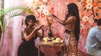 twee vrouwen gebruiken hun telefoon in een restaurant