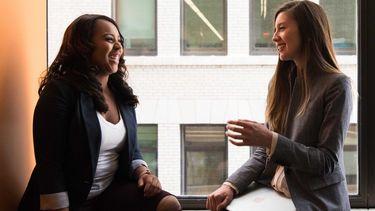 twee pratende vrouwen op kantoor, klagen collega's goed