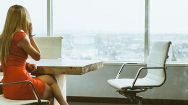 vrouw aan de top zit aan bestuurstafel te bellen