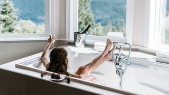 vrouw zit in bad met fles bubbels om successen te vieren