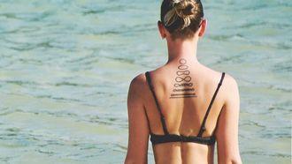 meisje met tattoos die op het strand zit, tattoo cliché